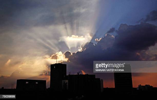Monsoon clouds loom over the Indian capital's skyline as the sun sets in New Delhi 05 July 2007 Large parts of India are experiencing heavy to very...