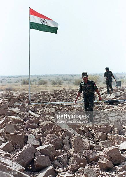 This file photo dated 20 May 1998 shows Indian soldiers walking on shattered ground as they patrol the edge of the crater at the Shakti1 site where...