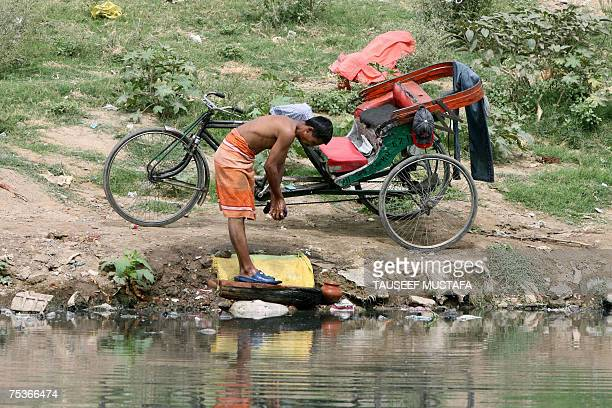 TO GO WITH INDIAENVIRONMENTPOLLUTION An Indian rickshaw driver washes clothes on the banks of the River Yamuna at Wazirabad on the outskirts of New...