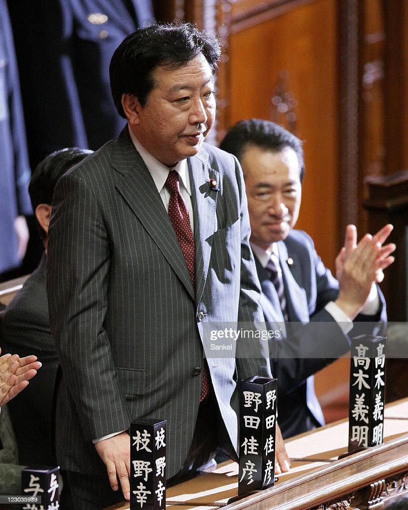 New Democratic Party of Japan (DPJ) President Yoshihiko Noda (L) stands after being elected as Japan's 95th Prime Minister while fellow lawmakers including Noda's predecessor Naoto Kan (R) applaud at the lower house on August 30, 2011 in Tokyo, Japan. Noda become the sixth Prime Minister in five years.