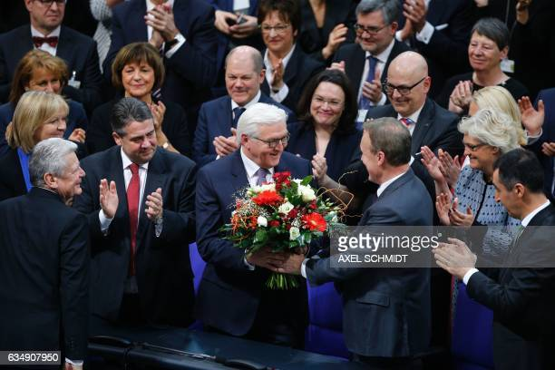 New elected German President FrankWalter Steinmeier is offered flowers by SPD parliamentary group leader Thomas Opperman as outgoing President...