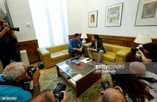New elected leader of Spanish Socialist Party Pedro Sanchez and leader of left wing party Podemos Pablo Iglesias chat as they pose before a meeting...