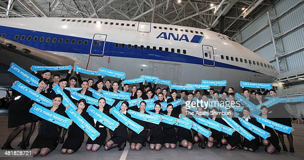 New employees of All Nippon Airways Co pose for photographs during a welcoming ceremony at the ANA's hangar on April 1 2014 in Tokyo Japan Japan's...