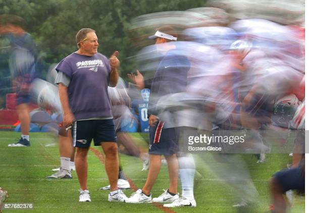 New England Patriots coach Bill Belichick chats with offensive coordinator Josh McDaniels as the team does stretching exercises during training camp...