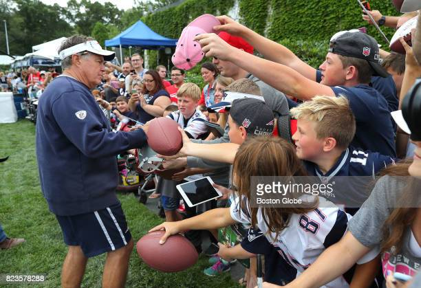 New England Patriots Coach Bill Belichick signs autographs at the end of the first day of training camp at the Gillette Stadium practice field in...