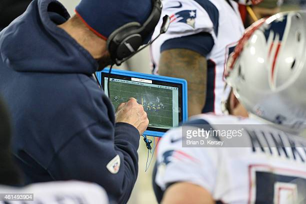 New England Patriots coach uses the Microsoft Surface tablet to go over plays during the fourth quarter against the Green Bay Packers at Lambeau...