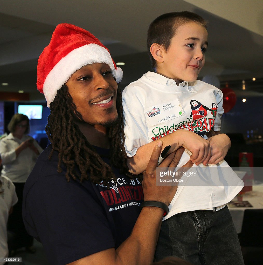 New England Patriots defensive back Marquice Cole gives a lift to Robby Leighton of Rochester, NH at the The New England Patriots Charitable Foundation host their 20th annual New England Patriots Children's Holiday Party at Gillette Stadium in Foxborough.