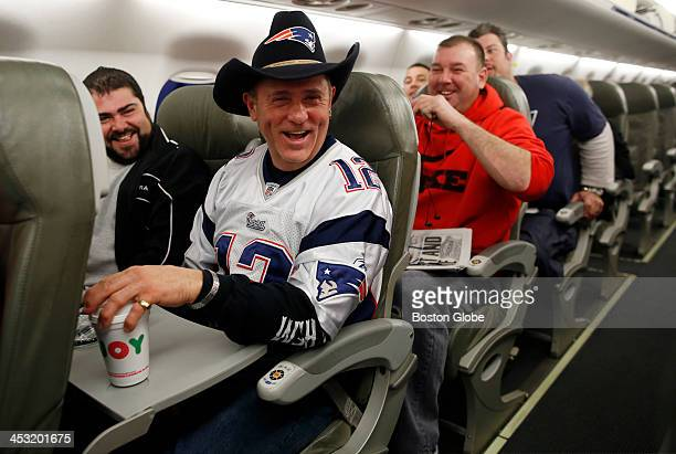 New England Patriots fans Bob Kovacev of Malden front center laughs as he sits next to Mark Capozzi of Windham NH on the plane to Houston Texas as...