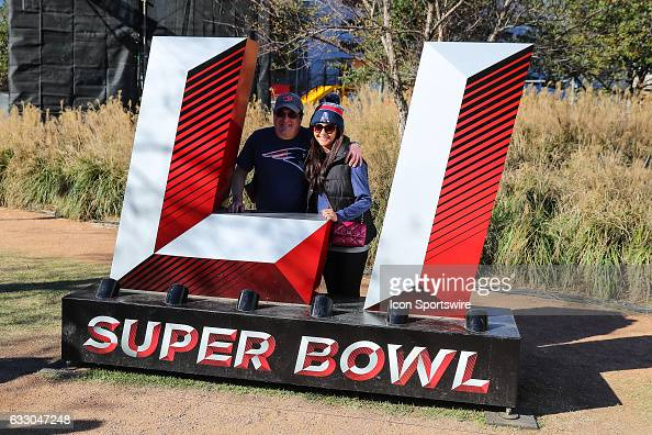 New England Patriots fans pose at the Super Bowl LI Logo inside the NFL Experience at the George R Brown Convention Center on January 29 in Houston...