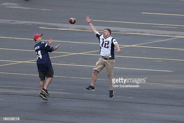 New England Patriots fans throw around a football on the parking lot outside the stadium before an NFL game against the Buffalo Bills at Ralph Wilson...