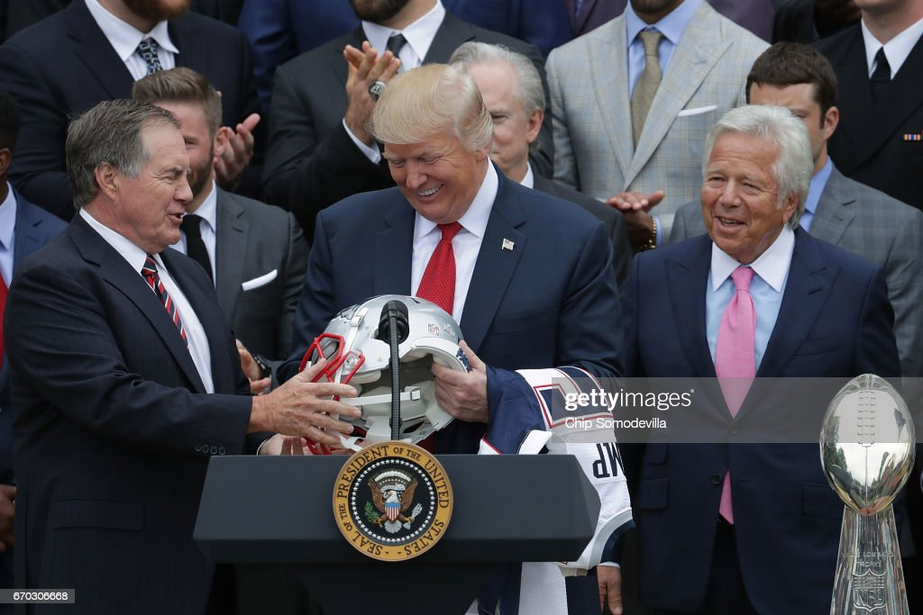 New England Patriots Head Coach Bill Belichick (L) and team owner Robert Kraft (R) present a football helmet to U.S. President Donald Trump during a celebration of the team's Super Bowl victory on the South Lawn at the White House April 19, 2017 in Washington, DC. It was the team's fifth Super Bowl victory since 1960.