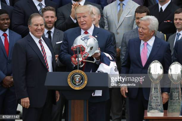 New England Patriots Head Coach Bill Belichick and team owner Robert Kraft present a football helmet to US President Donald Trump during a...