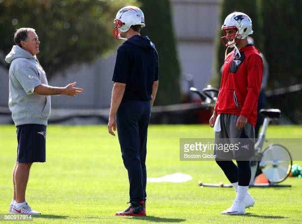 New England Patriots head coach Bill Belichick left talks with quarterback Tom Brady center and quarterback Jimmy Garoppolo right during practice at...