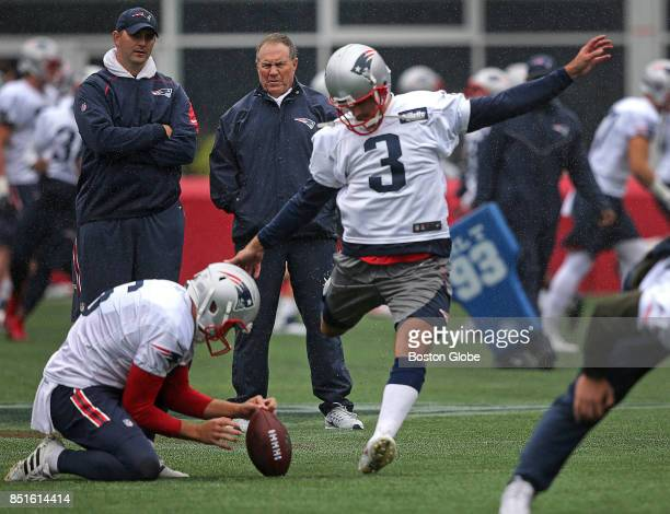 New England Patriots head coach Bill Belichick watches kicker Stephen Gostkowski kick field goals on the team's newly installed turf during practice...