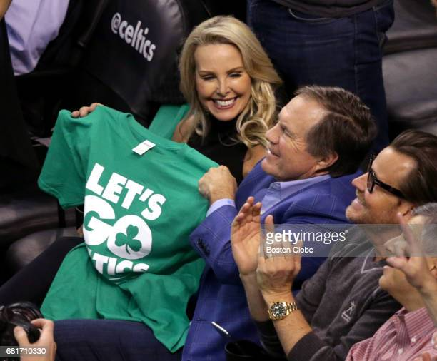 New England Patriots head coach Bill Belichick waves a Celtics Tshirt as his girlfriend Linda Holliday looks on during the fourth quarter The Boston...