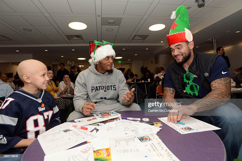 New England Patriots <a gi-track='captionPersonalityLinkClicked' href=/galleries/search?phrase=Patrick+Chung&family=editorial&specificpeople=2242933 ng-click='$event.stopPropagation()'>Patrick Chung</a> (C) and Mike Hoomanawanui visit with Camryn at Boston Children's Hospital December 9, 2014 in Boston, Massachusetts.