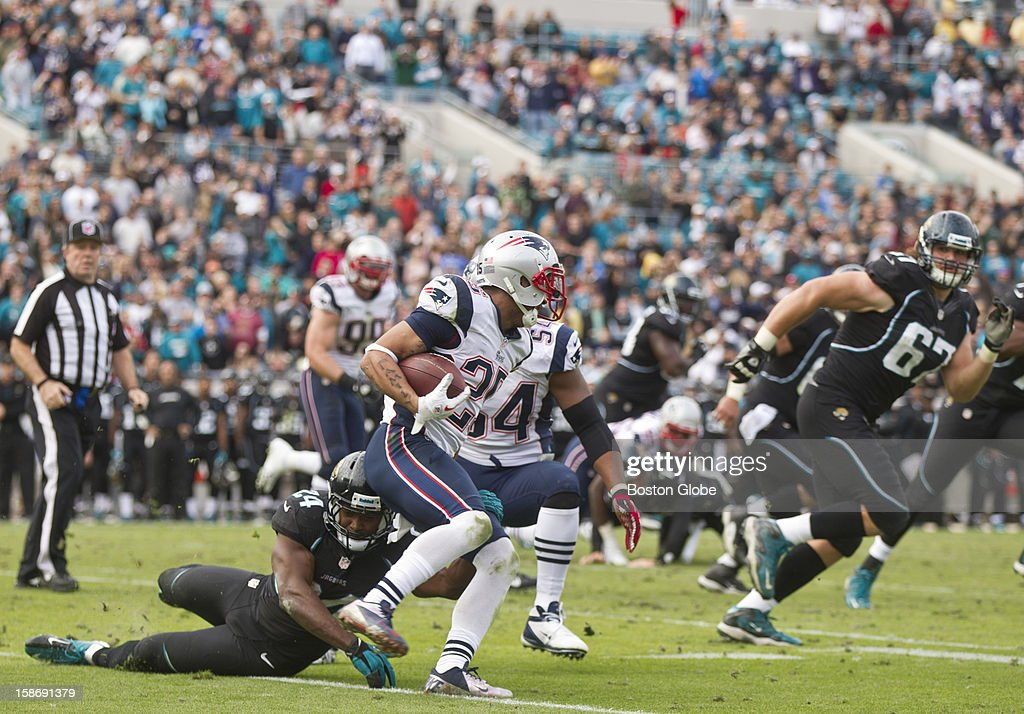 New England Patriots player Patrick Chung returns an interception in the end zone as he breaks the tackle of Jacksonville Jaguars Montell Owens during fourth quarter action at EverBank Field on Sunday, Dec. 23, 2012.