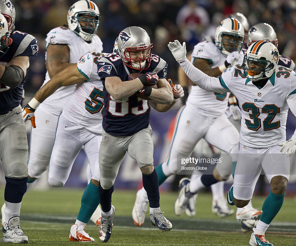 New England Patriots player Wes Welker picking up extra yards after a catch with pressure from Miami Dolphins Dimitri Patterson during first quarter action at Gillette Stadium on Sunday, Dec. 30, 2012.