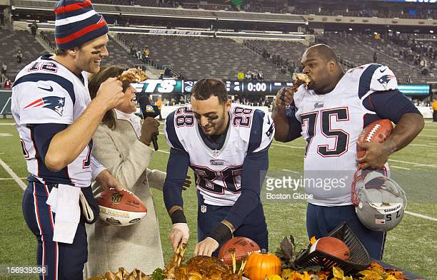 New England Patriots players left to right Tom Brady Steve Gregory and Vince Wilfork join television broadcaster Michele Tafoya eating turkey legs...