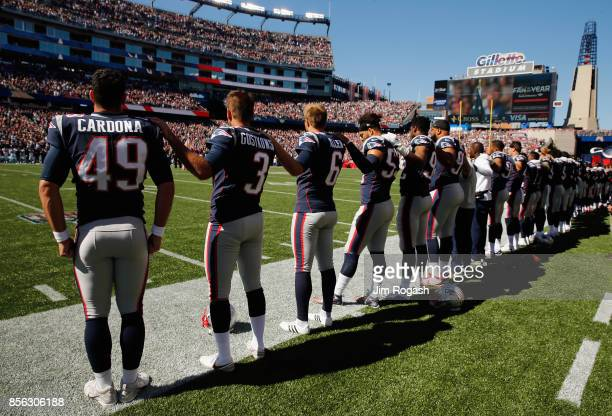 New England Patriots players stand for the national anthem before their game against the Carolina Panthers at Gillette Stadium on October 1 2017 in...