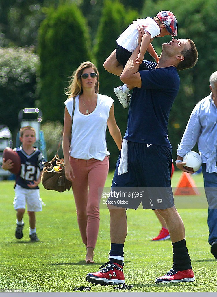New England Patriots quarterback <a gi-track='captionPersonalityLinkClicked' href=/galleries/search?phrase=Tom+Brady+-+Football-Spieler+-+Quarterback&family=editorial&specificpeople=201737 ng-click='$event.stopPropagation()'>Tom Brady</a> kisses his son, Benjamin, as his other son John, left, walks with Brady's wife, Gisele Bundchen, at the end of practice. The New England Patriots held practice with the New Orleans Saints at the practice fields during training camp.