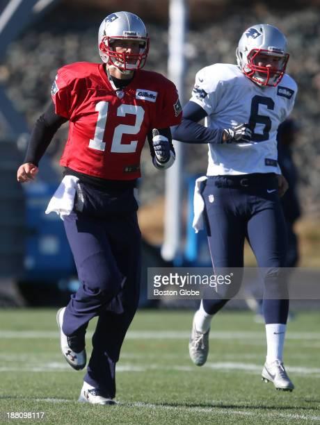 New England Patriots quarterback Tom Brady left with teammate Ryan Allen right at practice