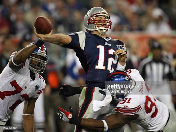 New England Patriots quarterback Tom Brady passes the ball despite Osi Umenyiora and Justin Tuck of the New York Giants during Super Bowl XLII at the...