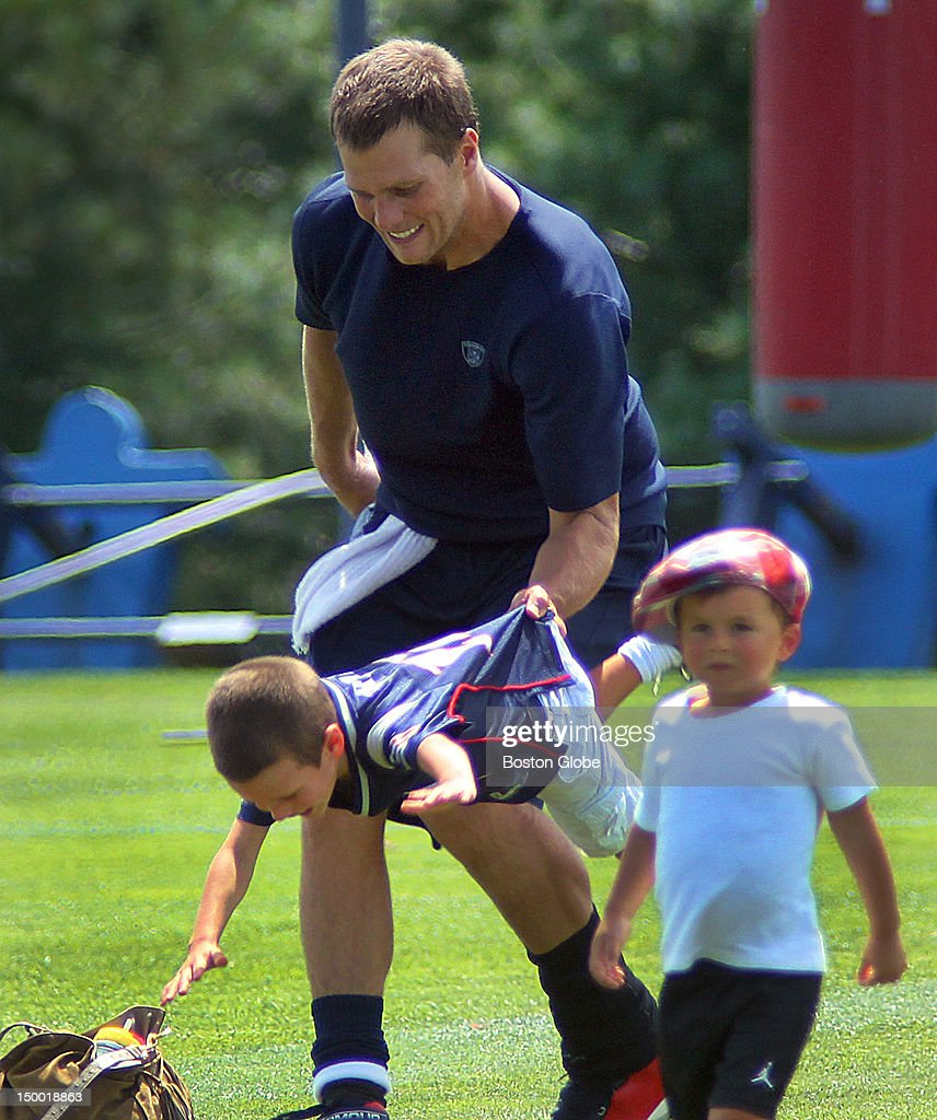 New England Patriots quarterback <a gi-track='captionPersonalityLinkClicked' href=/galleries/search?phrase=Tom+Brady+-+Amerikansk+fotbollsspelare+-+Quarterback&family=editorial&specificpeople=201737 ng-click='$event.stopPropagation()'>Tom Brady</a> picks up his son, John, by the shirts as his other son, Benjamin, right, walks away at the end of practice. The New England Patriots held practice with the New Orleans Saints at the practice fields during training camp.