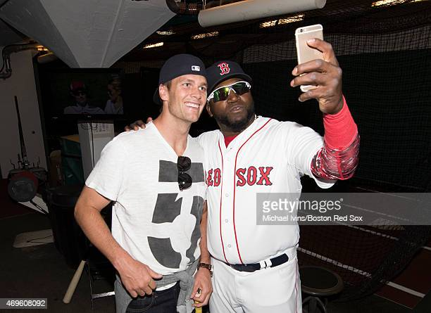 New England Patriots quarterback Tom Brady poses for a photograph with David Ortiz of the Boston Red Sox in the batting cage after throwing out a...