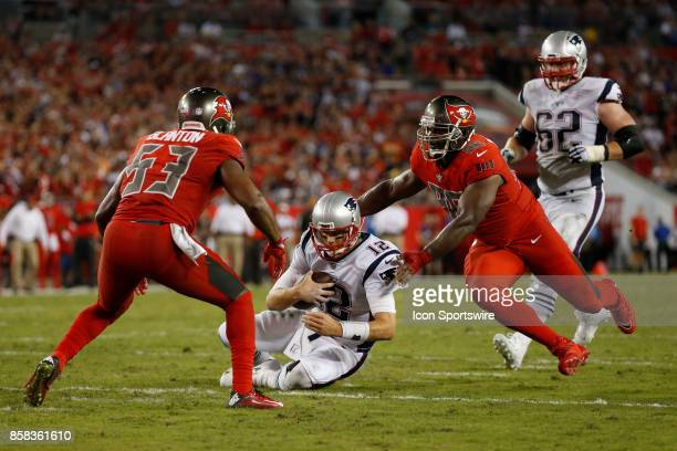 New England Patriots quarterback Tom Brady slides to avoid bing hit by Tampa Bay Buccaneers outside linebacker Adarius Glanton and Tampa Bay...