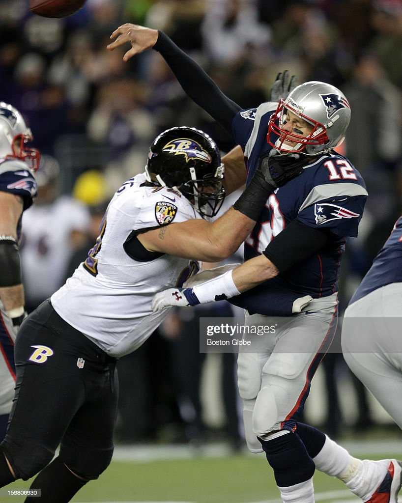 New England Patriots quarterback Tom Brady (#12) takes a hit as he just gets off a pass late in the fourth quarter as the New England Patriots hosted the Baltimore Ravens in the AFC Championship Game at Gillette Stadium.