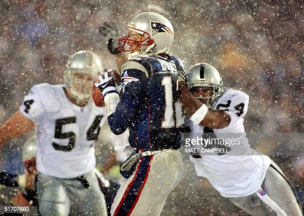 New England Patriots quarterback Tom Brady takes a hit from Charles Woodson of the Oakland Raiders on a pass attempt in the last two minutes of the...