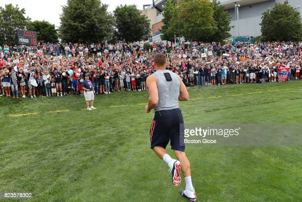 New England Patriots Rob Gronkowski runs over to fans to sign autographs after the first day of training camp at the Gillette Stadium practice field...
