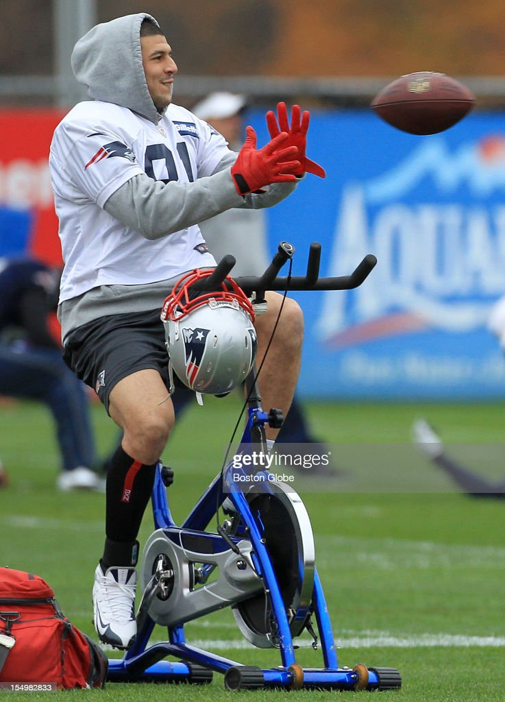 New England Patriots tight end <a gi-track='captionPersonalityLinkClicked' href=/galleries/search?phrase=Aaron+Hernandez+-+Joueur+de+football+am%C3%A9ricain&family=editorial&specificpeople=4586516 ng-click='$event.stopPropagation()'>Aaron Hernandez</a> (#81) shows off his multi tasking ability as he catches a pass while warming up on a bicycle at today's Patriots practice.