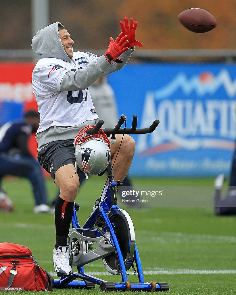 New England Patriots tight end Aaron Hernandez (#81) shows off his multi tasking ability as he catches a pass while warming up on a bicycle at today's Patriots practice.