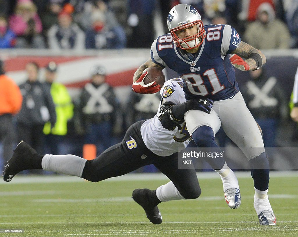 New England Patriots tight end Aaron Hernandez tries to elude the grasp of Baltimore Ravens inside linebacker Ray Lewis after making a reception...
