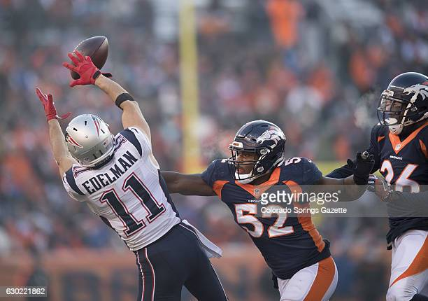 New England Patriots wide receiver Julian Edelman hauls in a pass in front of Denver Broncos defenders Corey Nelson and Darian Stewart in the first...