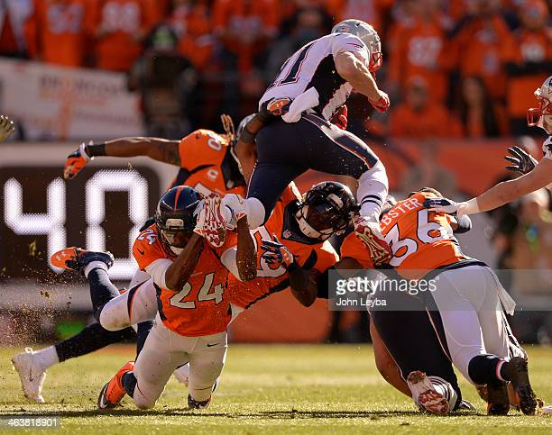 New England Patriots wide receiver Julian Edelman tries to leap over the Broncos but Denver Broncos cornerback Champ Bailey has him by the foot...