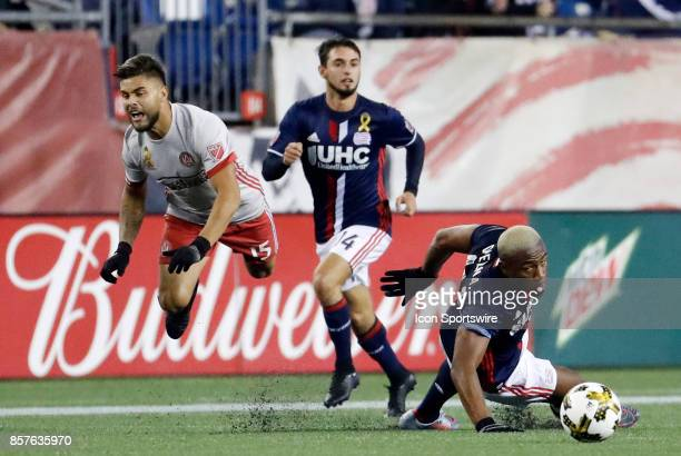 New England Revolution defender Claude Dielna takes out Atlanta United FC forward Hector Villalba during a match between the New England Revolution...