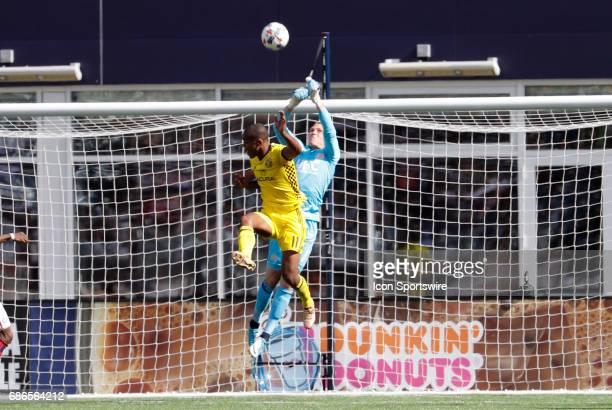 New England Revolution goalkeeper Cody Cropper rises to punch the ball away from Columbus Crew forward Ola Kamara during a regular season MLS match...