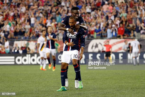 New England Revolution midfielder Teal Bunbury reacts to his second goal of the game as New England Revolution midfielder Gershon Koffie jumps on...