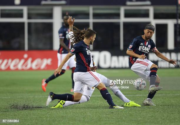 New England Revolution's Kelyn Rowe left and Lee Nguyen team up to displace the ball from Los Angeles Galaxy's Jermaine Jones during the first half...