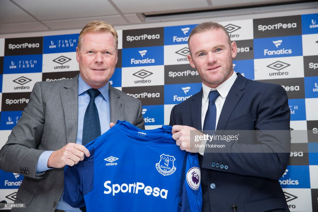 New Everton Signing Wayne Rooney is given his shirt by Manager Ronald Koeman at Goodison Park on July 10, 2017 in Liverpool, England.