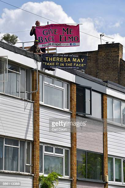 'New Fathers 4 Justice' campaigners hold banners as they protest on the roof of Labour leader Jeremy Corbyn's house on August 5 2016 in London...