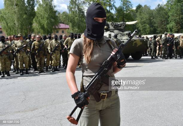 A new female volunteer recruit of the Ukrainian army 'Donbass' battalion takes a military oath during a ceremony of the National Guard unit near the...
