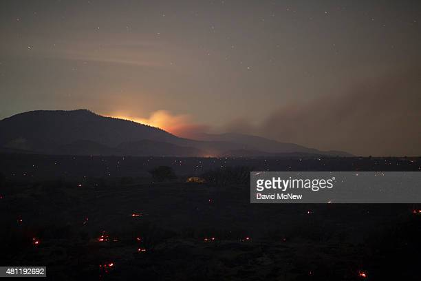 A new fire being dubbed the Pine Fire is seen in the distance as a landscape of embers burns in the wake of the North Fire which caused people to...