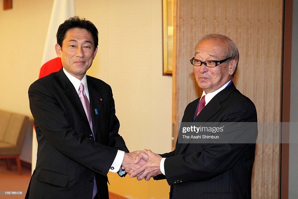 New Foreign Minister Fumio Kishida and Okinawa Prefecture Governor Hirokazu Nakaima shake hands prior to their meeting at Foreign Ministry on December 27, 2012 in Tokyo, Japan. Nakaima demands the resolution of U.S. Marine Corps Futenma Airbase relocation to the new administration.