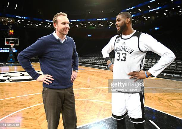 New General Manager Sean Marks talks to Willie Reed of the Brooklyn Nets before a game between the New York Knicks and the Brooklyn Nets on February...
