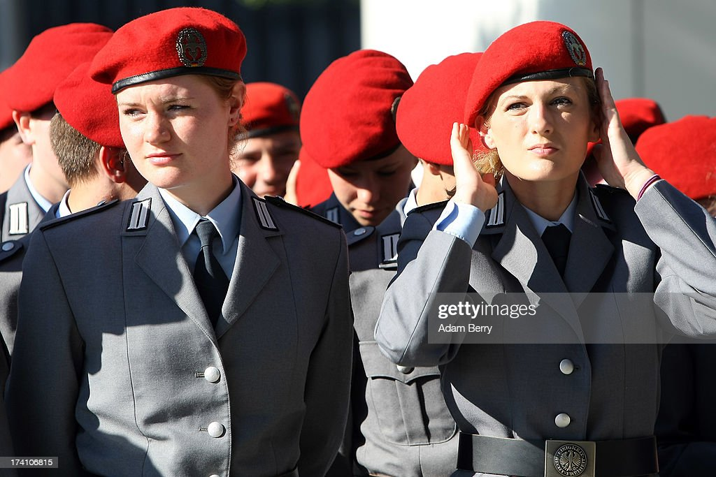A new German Bundeswehr soldier adjusts her hat prior to the start of a swearing-in ceremony for new recruits of the Bundeswehr, the armed forces of the Federal Republic of Germany, in front of the Reichstag building on July 20, 2013 in Berlin, Germany. In the annual ceremony, new soldiers take office on the anniversary of the assassination attempt on Adolf Hitler by Claus Schenk Graf von Stauffenberg.