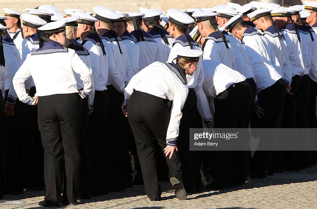 A new German Bundeswehr soldier stretches after standing at attention for an extended perior during a swearing-in ceremony for new recruits of the Bundeswehr, the armed forces of the Federal Republic of Germany, in front of the Reichstag building on July 20, 2013 in Berlin, Germany. In the annual ceremony, new soldiers take office on the anniversary of the assassination attempt on Adolf Hitler by Claus Schenk Graf von Stauffenberg.